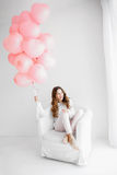 Woman sitting in an armchair and holding a bunch of pink balloons Stock Photo