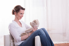 Woman sitting in armchair with teddy Stock Photography