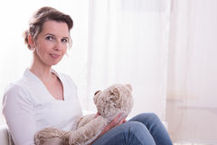 Woman sitting in armchair with teddy Royalty Free Stock Images