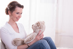 Woman sitting in armchair with teddy.  Royalty Free Stock Photo
