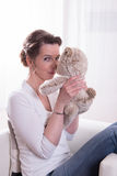 Woman sitting in armchair with teddy Stock Image