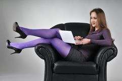 Woman sitting in armchair working. Portrait of young woman sitting in armchair working with netbook - studio shot Stock Image