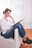 Woman sitting in armchair and working on file Royalty Free Stock Images
