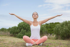 Woman sitting with arms raised on countryside landscape Stock Image