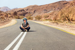 Woman sitting asphalt desert road. Stock Photo