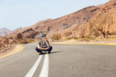 Woman sitting asphalt desert road. Stock Images