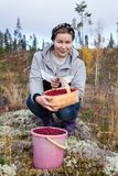 Woman sitting in autumn forest with a basket and a bucket full of ripe lingonberries Stock Photography