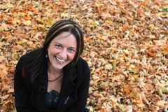 Woman sitting in autumn leaves Stock Images