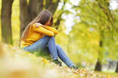 Woman sitting on autumn leaves stock photography