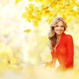 Woman sitting on autumn leaves. Happy young woman sitting on autumn leaves in park stock photos