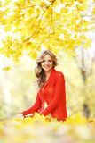 Woman sitting on autumn leaves. Happy young woman sitting on autumn leaves in park royalty free stock photography