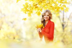 Woman sitting on autumn leaves. Happy young woman sitting on autumn leaves in park stock photo