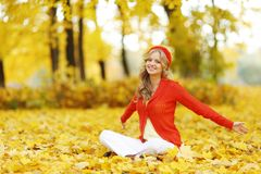 Woman sitting on autumn leaves. Happy young woman sitting on autumn leaves in park stock photography
