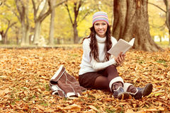 Woman sitting on the autumn leaves and reading book Stock Images
