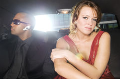 A woman sitting in the back of a car with her security guard stock photo