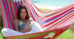 Woman sitting back in hammock while using phone stock video