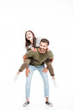 Woman sitting on back of her man. Cheerful women sitting on back of her strong men isolated Royalty Free Stock Photo