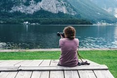 Woman sitting back on pier at lakeside. Woman sitting back on pier taking photographs at lakeside in Hallstatt in Austria looking at mountains stock photography