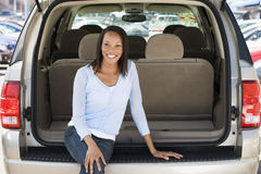 Woman sitting in back of van smiling Royalty Free Stock Photo