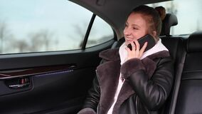 Woman is sitting in backseat of car taxi and talking on the phone
