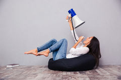 Woman sitting on bag chair and screaming in megaphone at herself Royalty Free Stock Photography