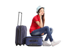 Woman sitting on bag and talking on phone Stock Photography