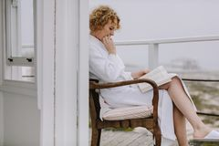 Woman reading a book sitting in balcony royalty free stock images
