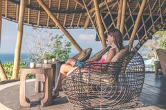 Woman sitting in bamboo restaurant. Original place. Space for text. Bali island. royalty free stock photos