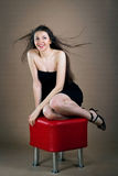 Woman sitting on banquette. Young woman in black dress sitting on red banquette Royalty Free Stock Images