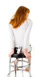 Woman sitting on a bar chair. With the cellphone Royalty Free Stock Photos