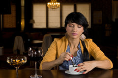 Woman sitting at a bar having coffee. Beautiful stylish young woman sitting at a bar having coffee stirring it with a spoon and looking down at the cup royalty free stock photo