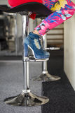 Woman sitting on bar stool in high heel ankle boots Royalty Free Stock Images