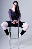 Woman sitting on bar stools. Beautiful girl in pointe sits on a bar stool Royalty Free Stock Images