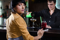 Woman sitting at a bar waiting to be served Stock Photography