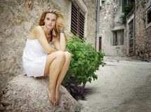 Woman sitting barefoot on street Stock Images