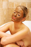 Woman sitting in bath with chocolate face mask Stock Photography