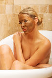 Woman sitting in bath with chocolate face mask Royalty Free Stock Images