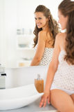 Woman sitting in bathroom and looking in mirror Royalty Free Stock Photography