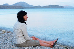 Woman sitting on the beach Stock Images