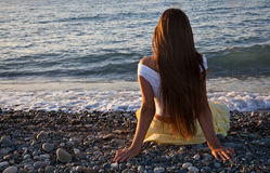 A woman is sitting on a beach Stock Images