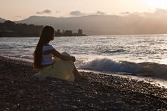 A woman is sitting on a beach Stock Photos