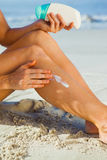 Woman sitting on the beach applying suncream Royalty Free Stock Photography