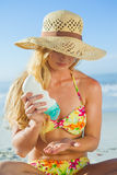 Woman sitting on the beach applying suncream Royalty Free Stock Images