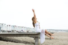 Woman sitting at the beach with arms raised Stock Photography