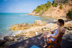 Woman sitting on beach-chair beside nice beach Stock Images