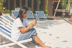Woman sitting on beach chair and playing smartphone at outside. stock images