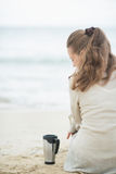 Woman sitting on beach with cup of hot beverage Stock Images