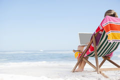 Woman sitting on beach in deck chair using laptop Stock Photography
