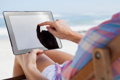 Woman sitting on beach in deck chair using tablet pc Royalty Free Stock Photography