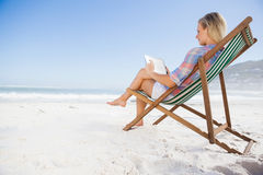 Woman sitting on beach in deck chair using tablet pc Royalty Free Stock Photo
